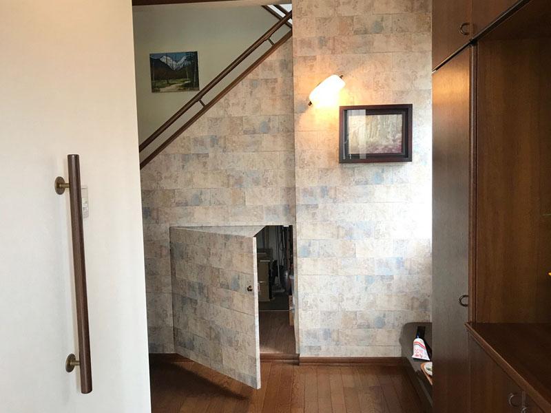 玄関の階段下に収納用扉の新設工事。玄関ホールの壁を一部解体し、階段下収納用の扉を設置しました。H様が選定したデザインクロスを扉にも貼り、扉と壁が一体化した雰囲気に仕上がりました。